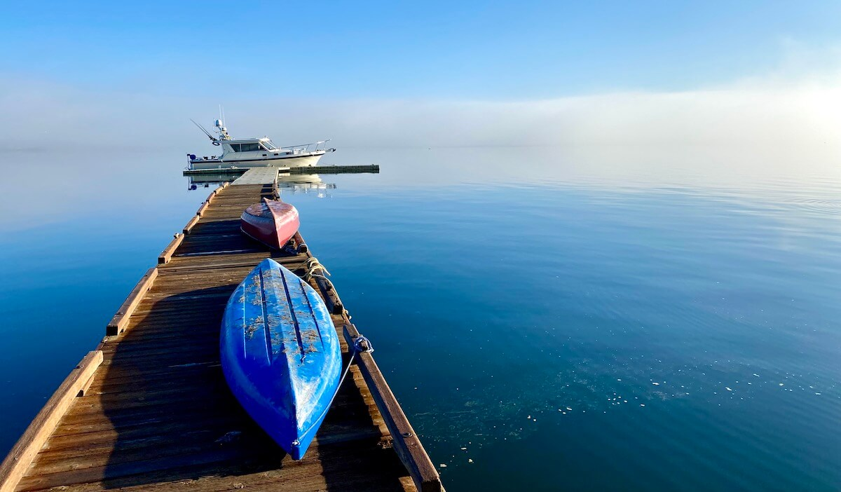 The boat slip at Captain Whidbey Hotel is one of the charming features of this unique Pacific Northwest hotel. There is a blue and red canoe on the dock and a cruising boat is tied to the end of the pier. The water is smooth and seems to fade into the mist.