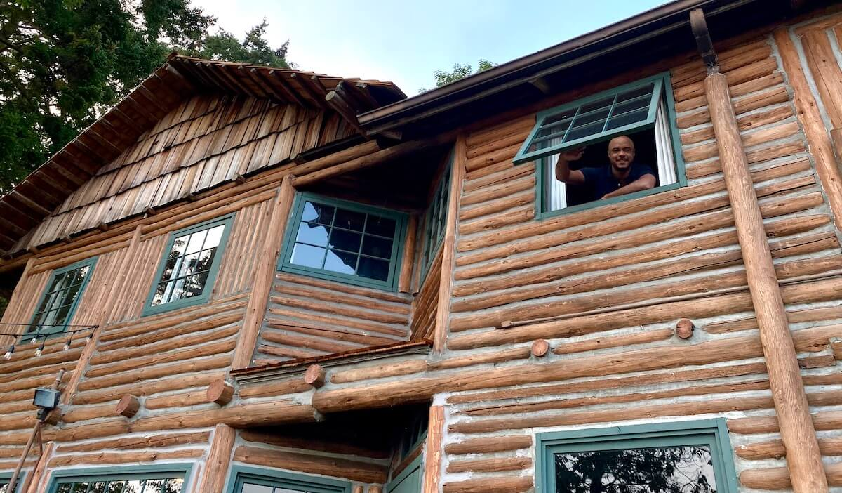 An African American man leans out a green paned window looking from the second floor of historic Captain Whidbey Inn, a unique Pacific Northwest hotel to visit. The logs on the wall of the two story structure are fused together with cement. the sky is blue.