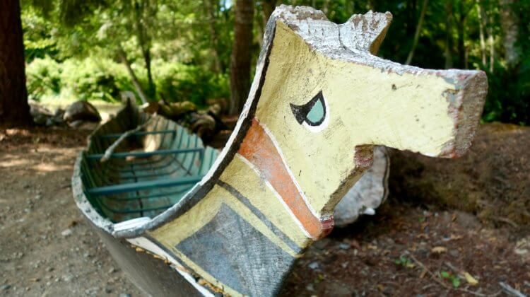 A traditional canoe used by Coast Salish People, carved from cedar and painted with ceremonial colors. In this case the bow is yellow with orange and black markings.