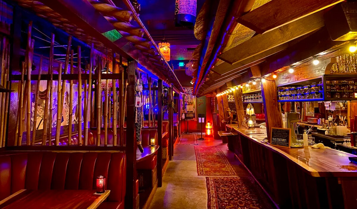 The Old Hangout in the basement of the McMenamins Elks Temple in Tacoma is a unique place to stay in the Pacific Northwest. The bar looks like a tiki theme and is dimly lit with candles at each table.