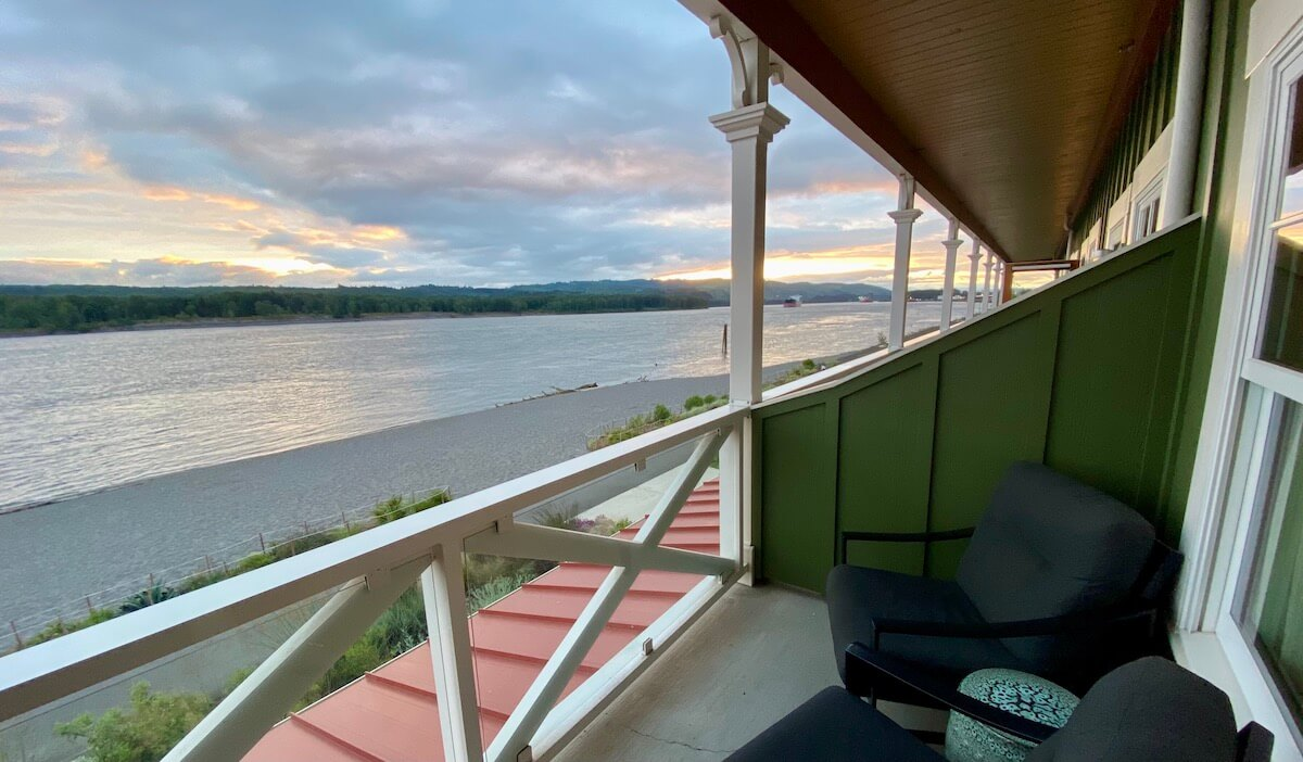 A veranda view of the Columbia River from the McMenamins Kalama Lodge. The sun is setting and there is a beach along the river below.