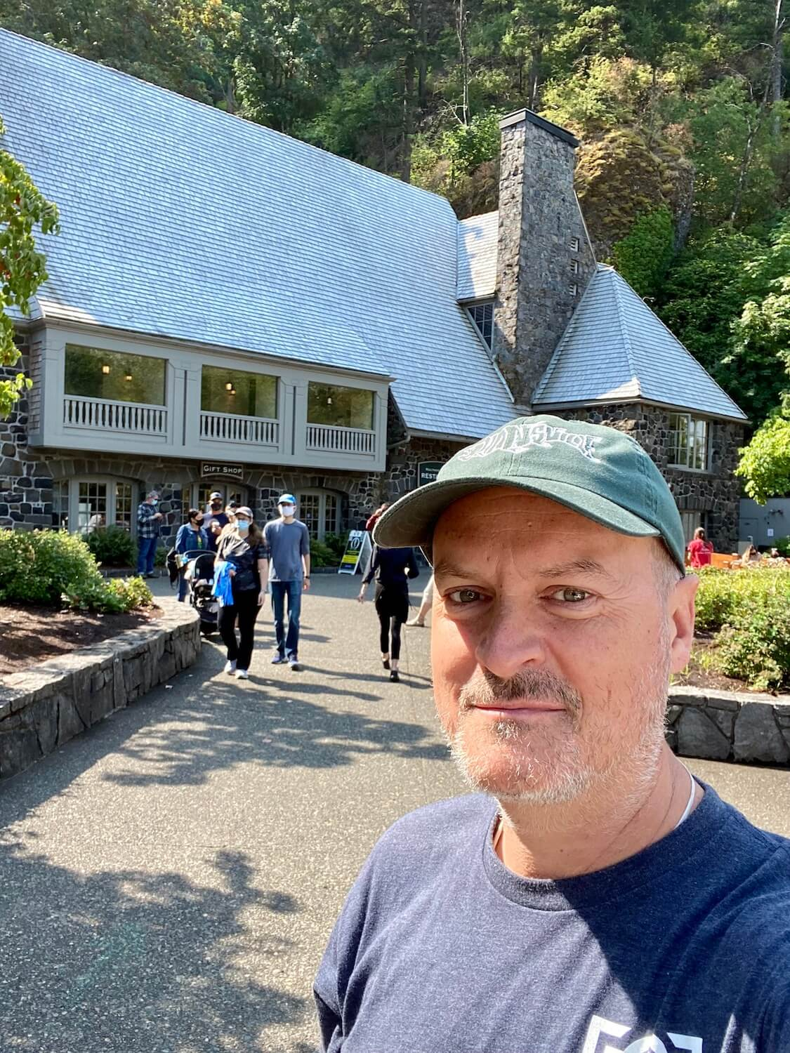 Matthew Kessi takes a selfie at Mulnomah Falls Lodge. There are people coming out of the lodge, which has a large stone fireplace and sweeping shake roofline.
