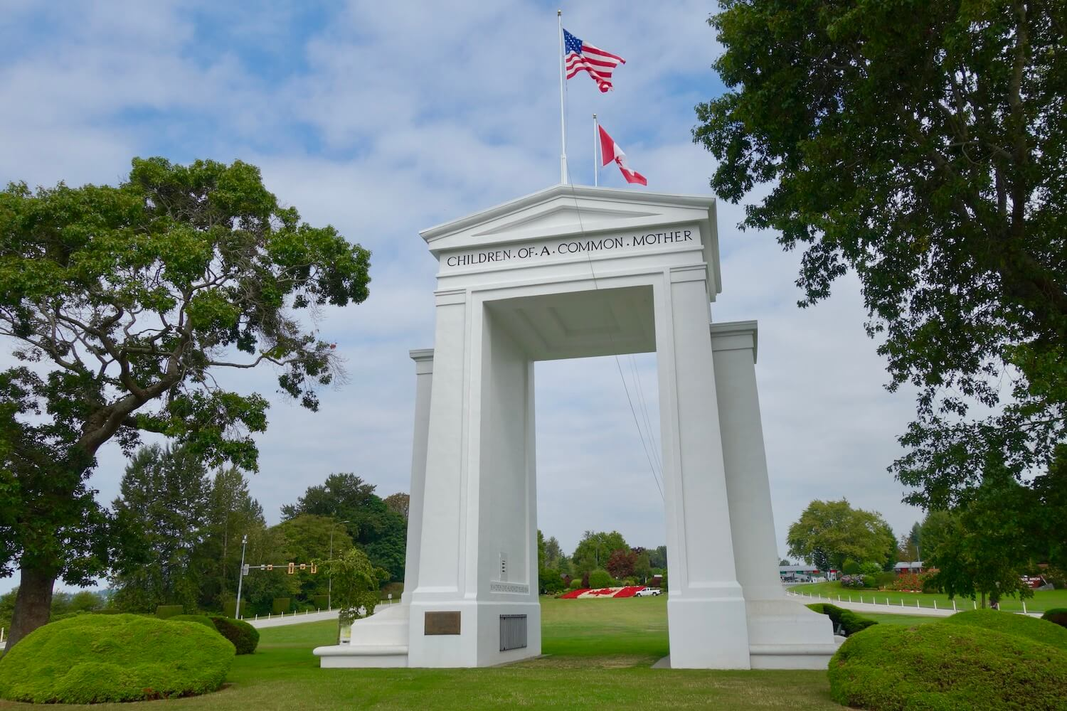 The giant Peace Arch at the United States Canada border is a milestone along the Seattle to Vancouver Drive. The giant white marble columns are located on a grassy green lawn with trees and gardens and both the US and Canadian flags fly proudly overhead.