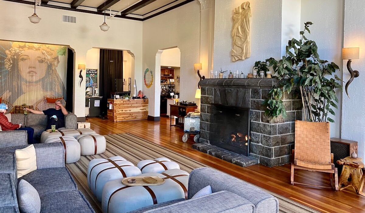 The lobby of the SCP Hotel in Redmond is very stylish with plush couches and pillows in front of a cozy fireplace.