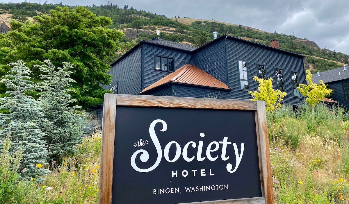 A sign for the Society Hotel in Bingen Washington stands in front of the dark painted hotel building, which used to be an old school. There is a lot of plant life used in the landscape around the hotel. The sky is dark and stormy.