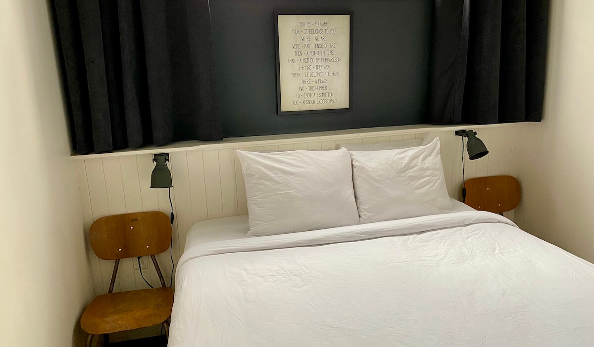 The pristine white linens of a room at the Society Hotel in Bingen Washington. There are two school chairs on either side of the bed and laps with flip switches. The wall has slate colored blinds and a framed poster.