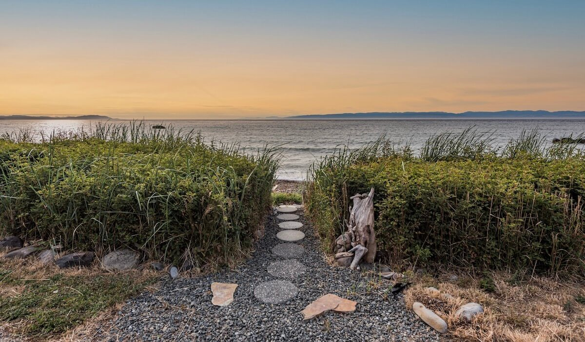Strait Surf Cabins is a great place to stay in the Pacific Northwest. Here, stone pavers lead a path through the sea grass to the water. The sunset is creating a peach colored sky with the ripples of the Strait of Juan de Fuca shining on.