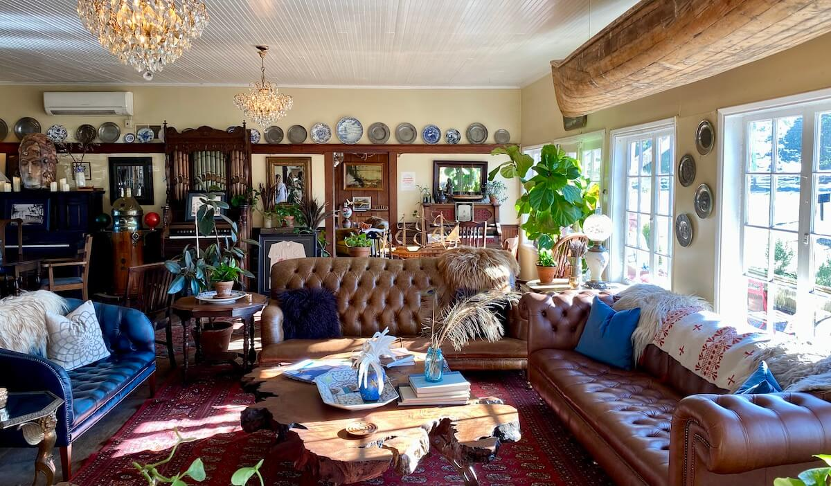 The eclectic lobby of the Tokeland Hotel stimulates the mind. On the back wall there are numbers of plates lining a railing while the foreground has plush couches with a large wood coffee table filled with books.