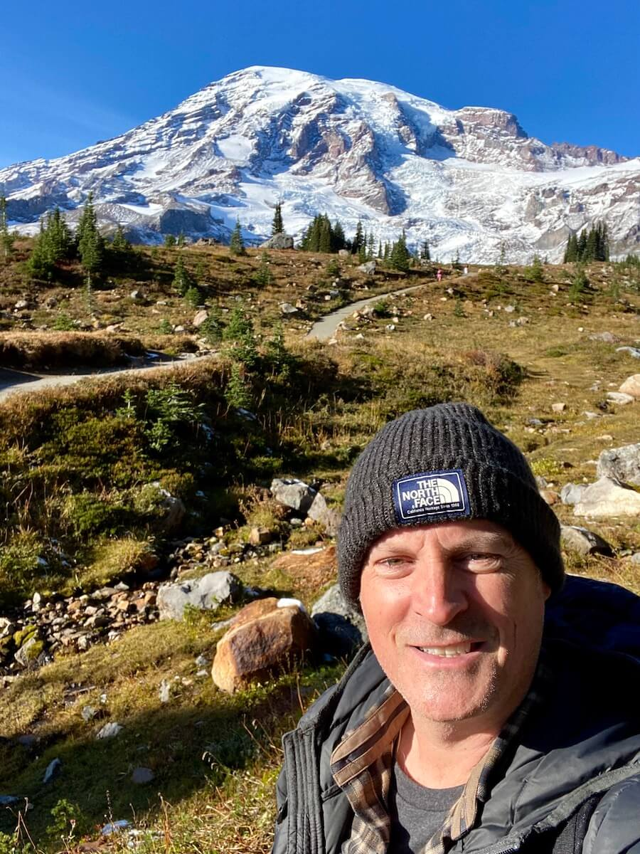 Matthew Kessi poses for a selfie while hiking on a trail on Mt. Rainier. The mountain is covered in snow and pops against the blue sky.