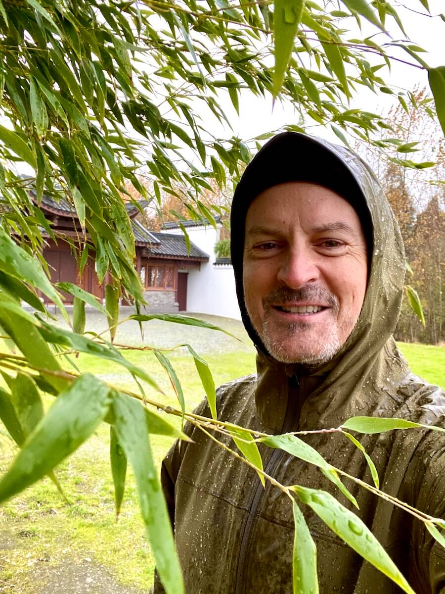 Matthew Kessi smiles for a selfie, covered in water from a rainstorm. He's standing under a bamboo plant with a Chinese pagoda in the background.