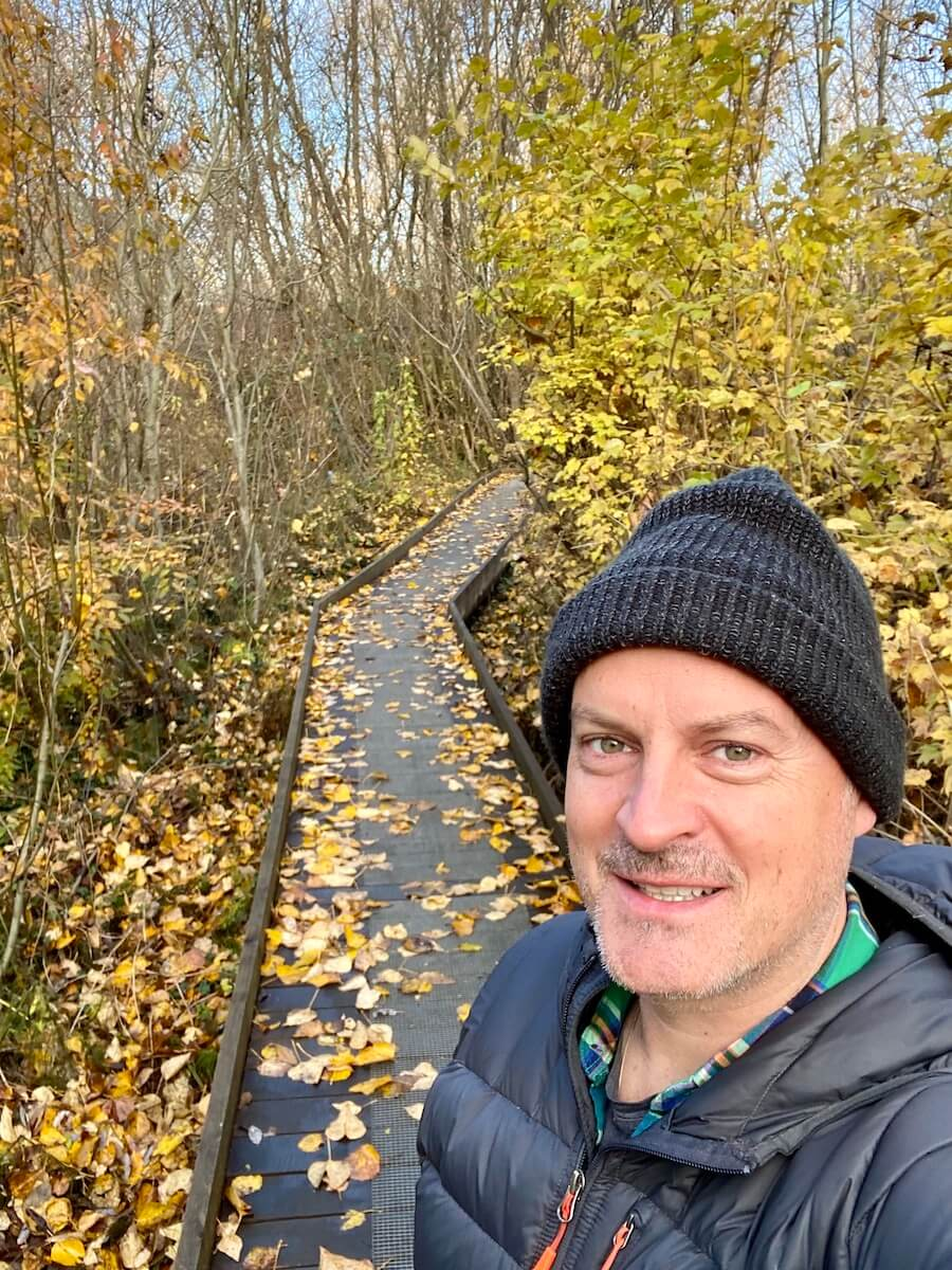 Matthew Kessi stands on a plank trail leading into a woods with trees losing their bright yellow leaves. He's smiling and dressed for November weather.